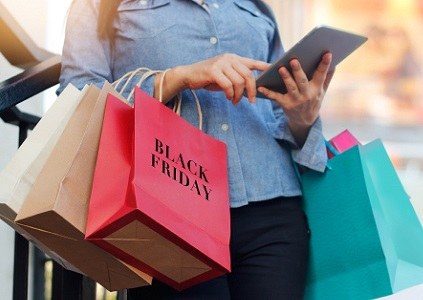 Woman with Black Friday bags shopping online with a tablet