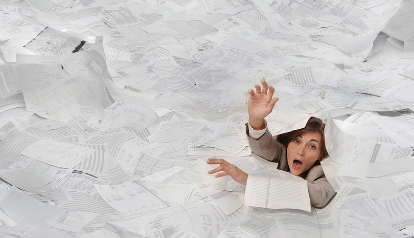 Someone drowning in a sea of information and paper