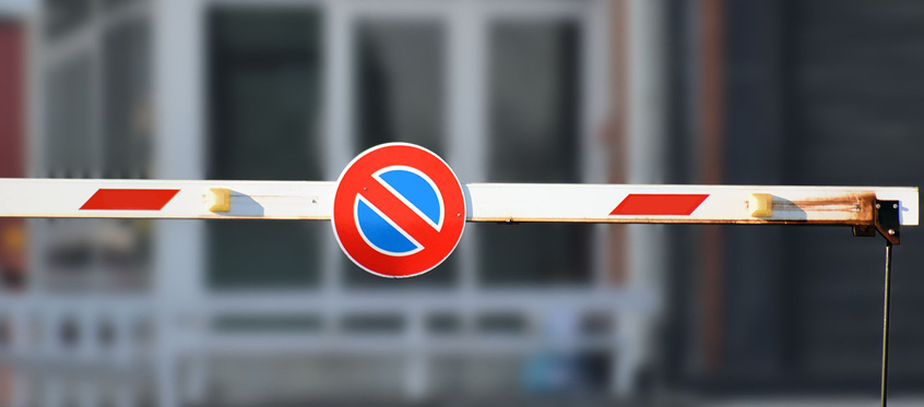 A no-entry sign on a parking barrier gate