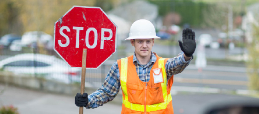 A traffic conductor holds a stop sign