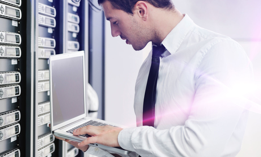 Man in data center working on a laptop